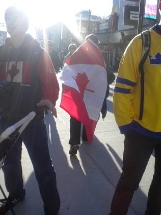 캐나다 국기를 등에 두르고 길을 가는 사람