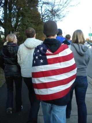 미국 국기를 등에 두르고 길을 가는 사람