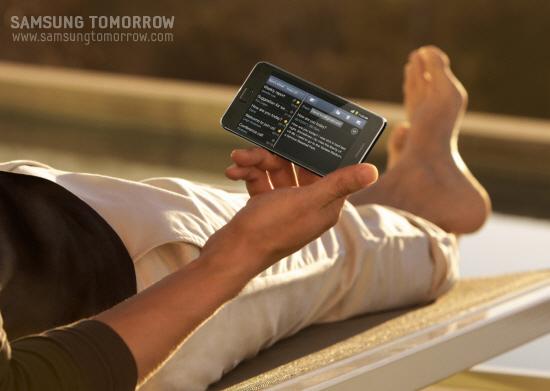 편하게 누워 갤럭시S2를 사용하고 있는 모습