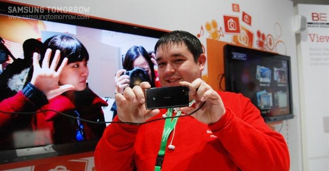 소니 에릭슨 부스의 직원이 스마트폰으로 사진을 찍어주고 있다
