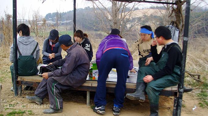 원두막에 모여 점심식사를 하는 봉사단원들