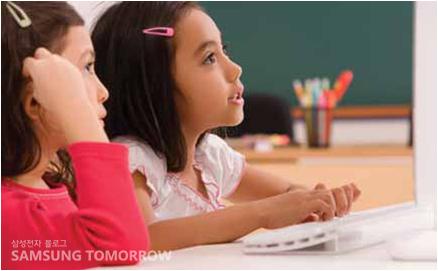 컴퓨터로 공부를 하고 있는 외국의 어린아이