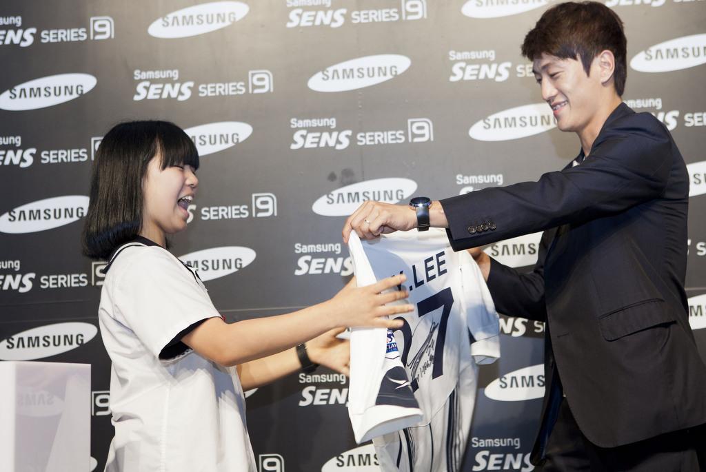 이청용 선수가 팬에게 사인 유니폼을 선물하고 있다