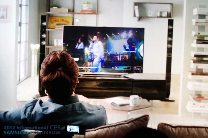 남자가 소파에 앉아 티비를 보는 장면