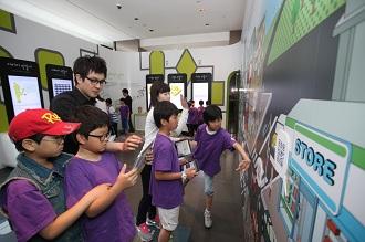 아이들이 소프트웨어체험관에서 다양한 기구들을 체험해보고 있다