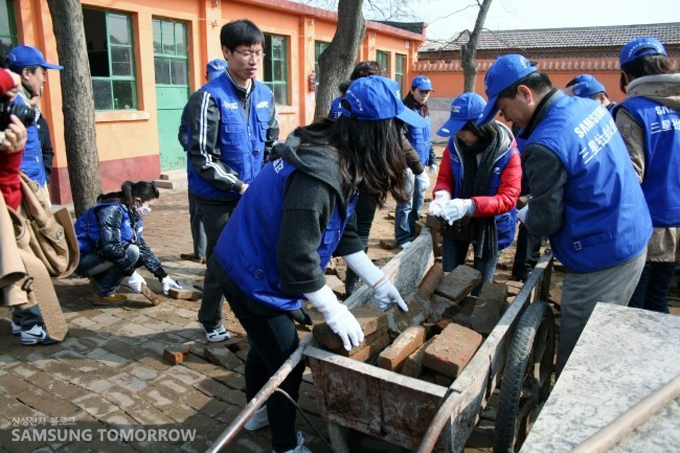삼성 임직원들이 벽돌을 수레에 실어서 나르고 있다