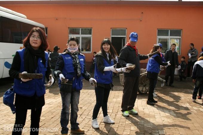 삼성 임직원들이 줄지어 서서 벽돌을 나르고 있다