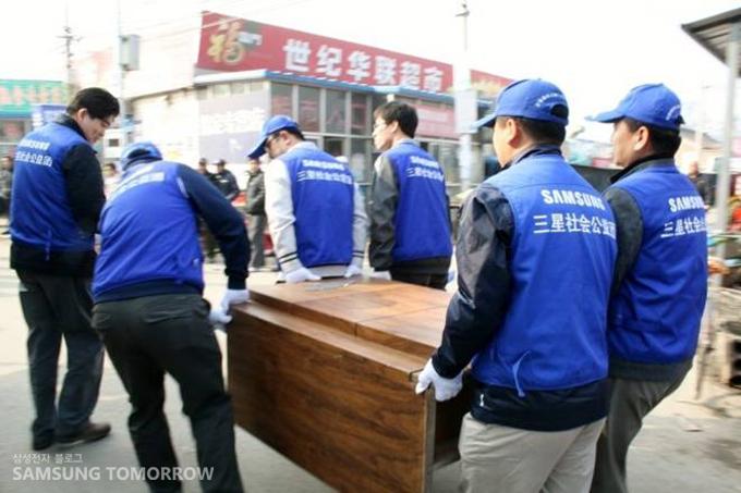 파란 옷을 입은 삼성 임직원들이 단상을 나르고 있다