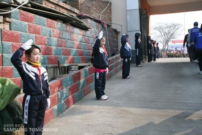 학교 입구에서 교복에 빨간 스카프를 두른 명성학교 학생들이 경례를 한 채 학교를 찾아준 삼성 임직원들을 맞아주고 있다