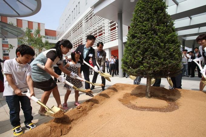 삼성전자 디지털시티 어린이집 개원 기념으로 나무를 심고 있는 모습