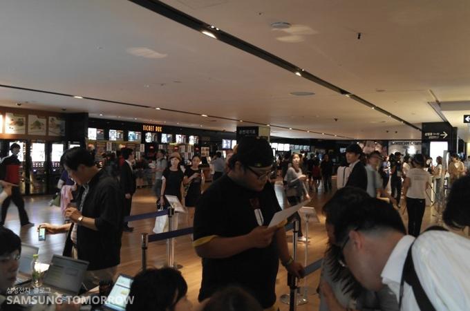 삼성 스마트카메라 출시기념 'SEND 무지 콘서트'가 준비되어 있는 영화관 앞 사람들이 붐비고 있는 모습