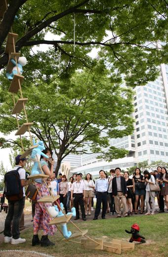나무사다리 조각을 보고 있는 직원들의 모습