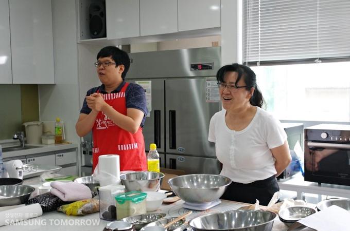 싱크대와 오븐이 있는 주방에 선생님과 진행자가 있는 모습