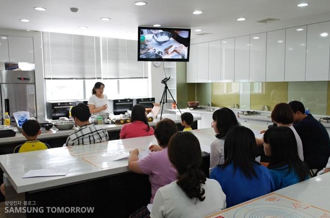 화면을 보며 화과자 요리방법을 설명하는 선생님의 설명을 듣는 모습