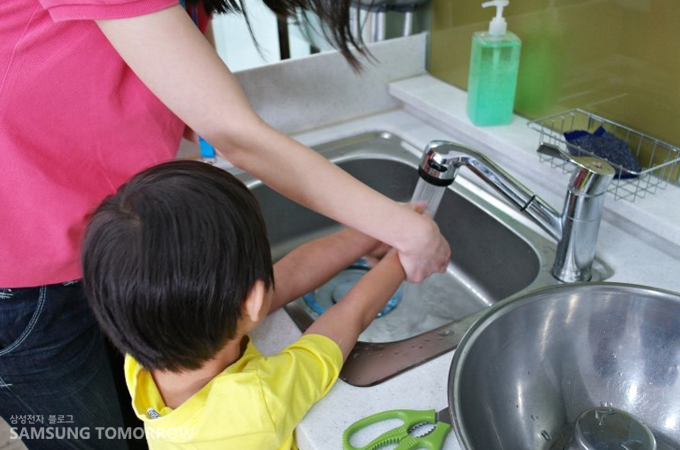 요리에 앞서 아이의 손을 씻겨주는 모습