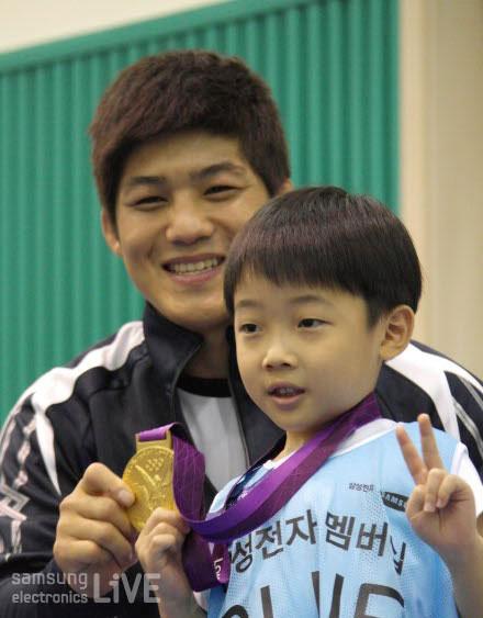 김현우 선수가 어린이에게 금메달을 쥐어주며 함께 포즈를 취하고 있다