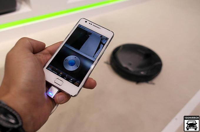 스마트폰으로 로봇 청소기 카메라로 보이는 화면을 보고 있다