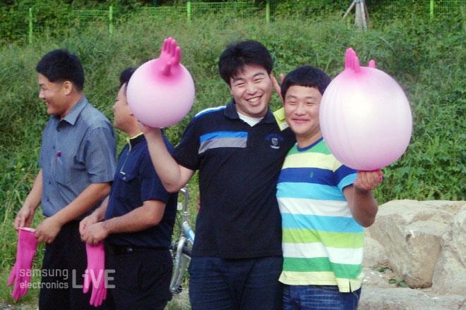 고무장갑을 풍선처럼 만들어서 사진을 찍은 직원들의 모습