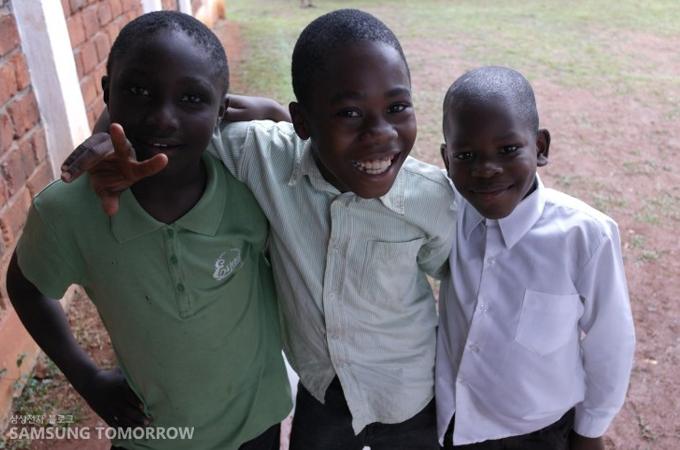 치료를 받고 나와 카메라를 보며 환한 웃음을 짓고 있는 카메룬의 아이들