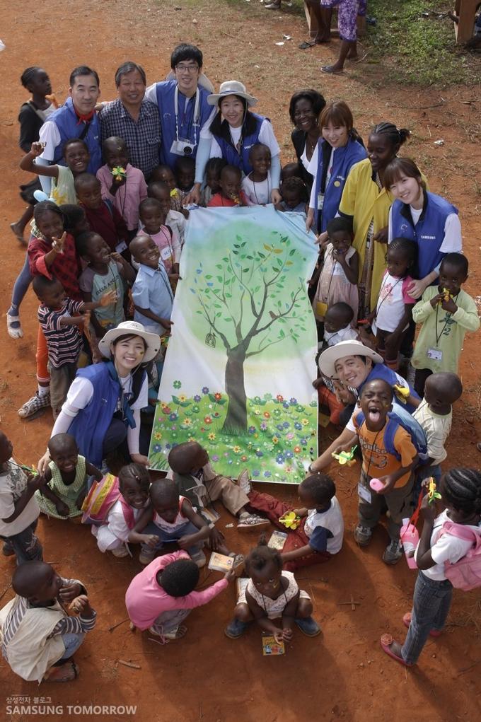 아이들의 손으로 완성된 멋진 나무그림을 들고 찍은 단체사진