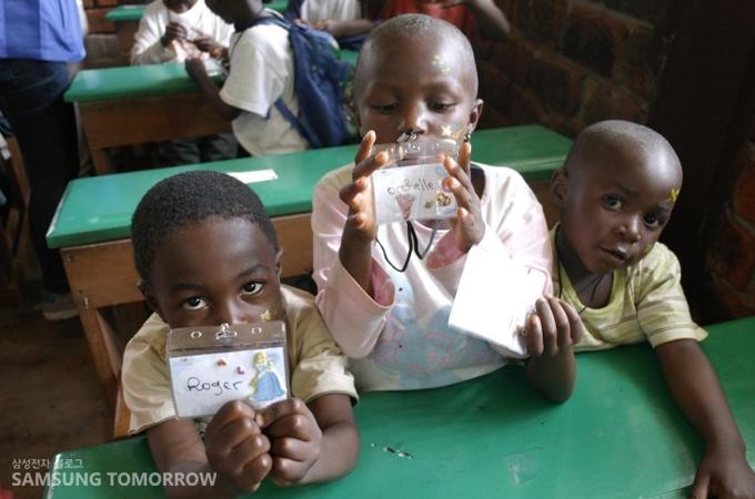 직접 만든 이름표를 들고 있는 아이들의 모습
