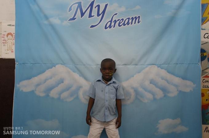 천사날개가 그려진 현수막 앞에서 있는 아이의 모습