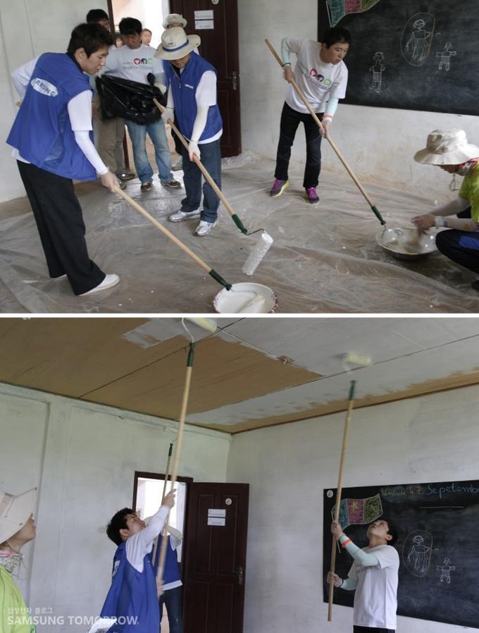 천장과 바닥에 하얀페인트칠을 하고 있는 봉사단의 모습