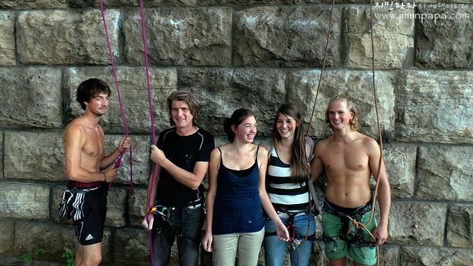 돌담앞에 서서 사진을 찍는 사람들