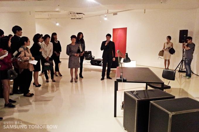 타임리스 디자인전 전시회를 보고 있는 사람들의 모습