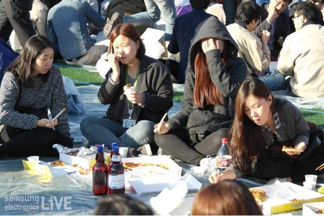 돗자리에 앉아 피자를 먹는 직원들