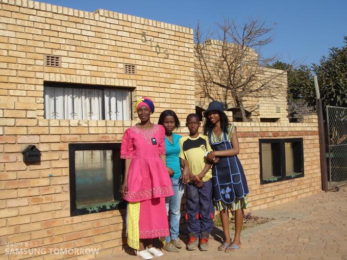 벽돌집 앞에서 찍은 Lefa와 엄마, 언니, 남동생의 사진