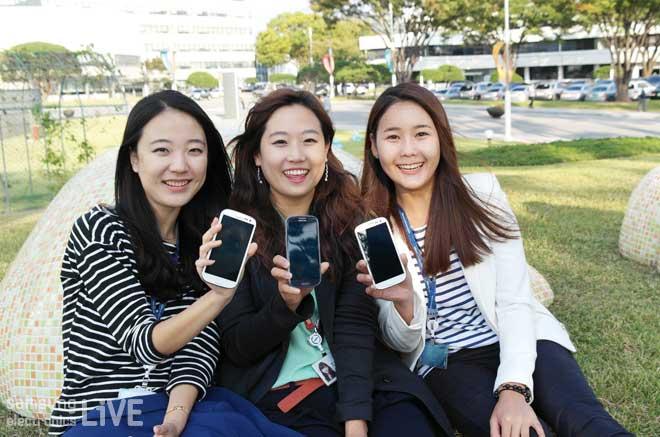 스마트 폰을 들고 있는 세 여성