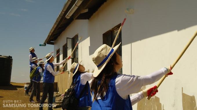 학교의 외벽을 하얀색 페인트로 칠하고 있는 봉사단들
