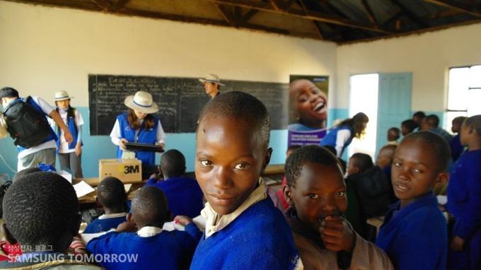 교실에 모인 아이들과 카메라를 응시하는 아이들