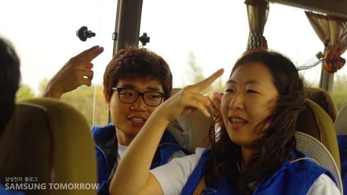 버스에서 율동을 연습하는 봉사단원들