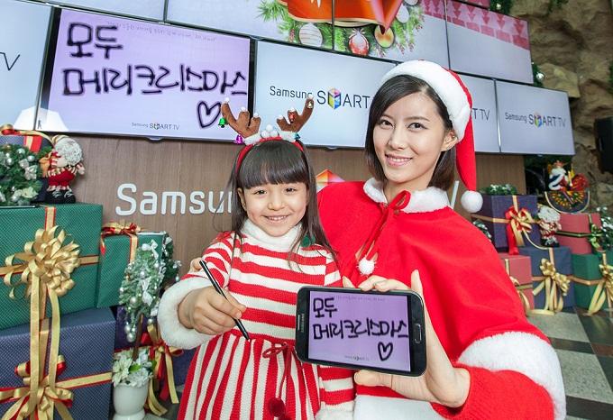 잠실에 설치된 '올쉐어트리' 앞에서 어린아이와 '모두 메리크리스마스'메시지를 전달하고 있는 모델의 모습