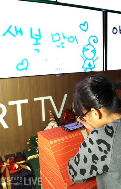갤럭시 노트2를 이용하여 삼성 스마트TV에 메시지를 적고있는 아이