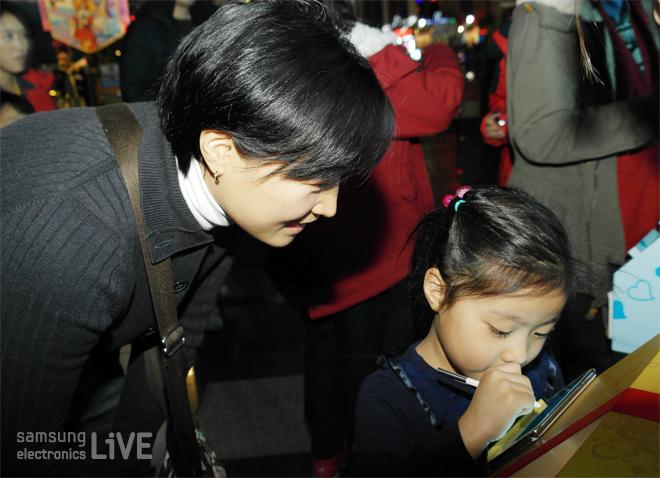 올쉐어 트리 이벤트에 참가하고 있는 아이와 엄마