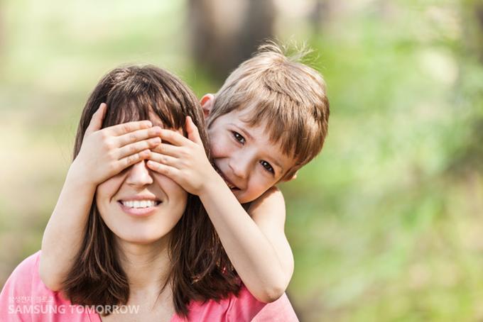엄마의 눈을 뒤에서 손으로 가리고 있는 아이의 이미지