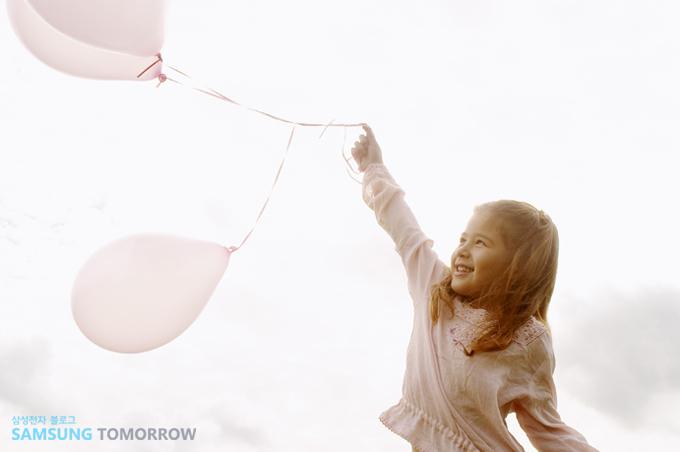 여아이가 풍선을 들고 있는 모습입니다.