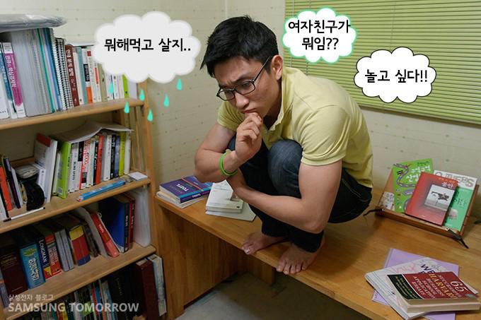 삼성스토리텔러 김지용군이 책상 위에 쭈그려 앉아 고민하고 있는 이미지입니다. '뭐해먹고 살지? 여자친구가 뭐임?? 놀고싶다!!'