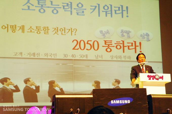 박근희 삼성생명 부회장이 무대 위에서 강연하고 있는 이미지 입니다. 무대 위에는 '소통 능력을 키워라! 어떻게 소통할 것인가? 2050통하라! (몽니 움짤 안물)' 이라고 써져 있습니다.