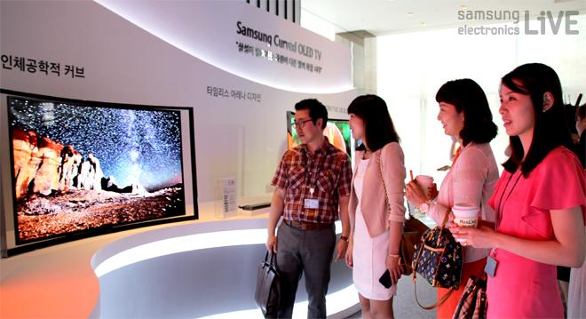 참가자들이 삼성 OLED TV를 살펴보고 있다