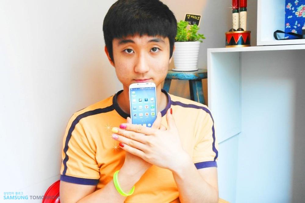 삼성스토리텔러 김지용이 갤럭시S4를 든 채 손톱엔 매니큐어가 발려져 있습니다.