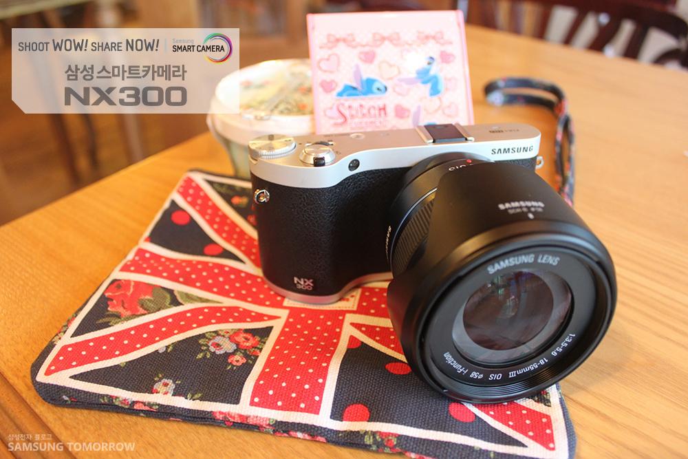 삼성스마트카메라NX300이 테이블 위에 올려져 있습니다.