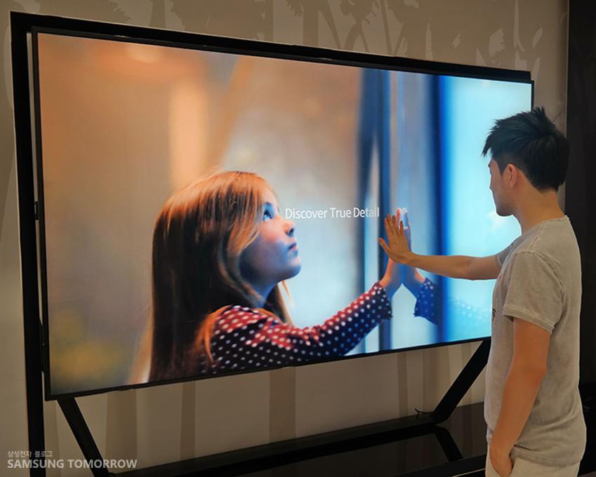 삼성스토리텔러 영재가 UHD TV에 손을 가져다 대고 있습니다.