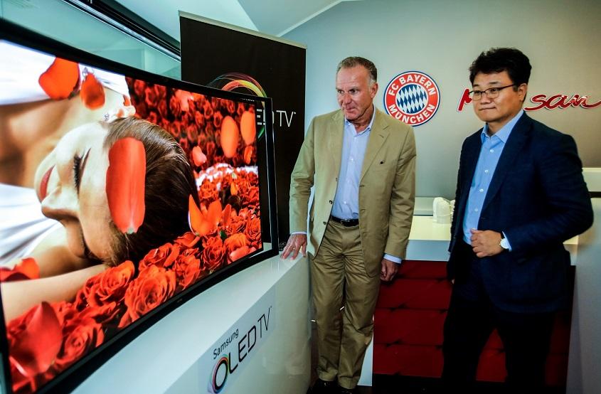 삼성전자 독일 법인장 김동민 상무가 커브드 OLED TV 유럽 1호 고객인 FC바이에른 뮌헨 칼 하인츠 루메니게 CEO에게 제품을 전달하고 있습니다.
