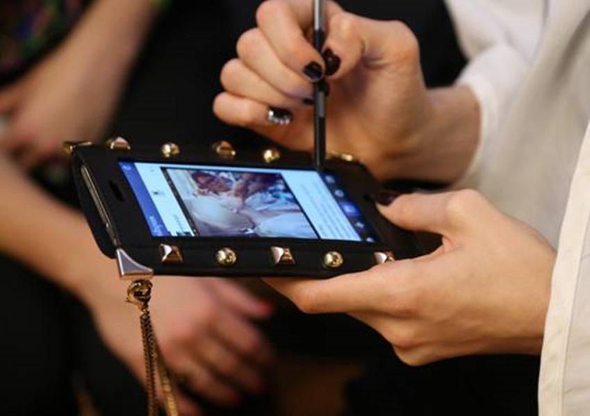 뉴욕패션위크에서 스터드 장식이 달린 케이스를 씌운 갤럭시 노트3를 사용하는 모습입니다.
