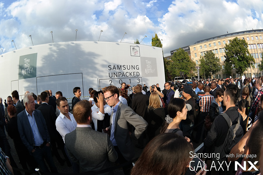 삼성 모바일 언팩 행사장 앞에서 사람들이 입장을 기다리며 이야기를 나누고 있습니다.
