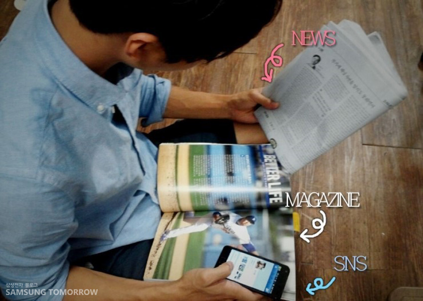 양 손에 신문과 잡지, SNS를 보기 위해 휴대폰을 들고 있는 모습입니다.